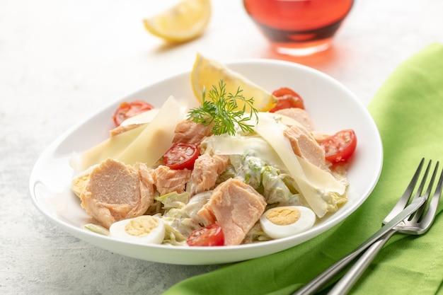 Insalata con salmone al forno. una grande porzione di insalata con pesce rosso, verdure fresche, uova, pomodorini e limone. concetto per un alimento chetogenico gustoso e sano