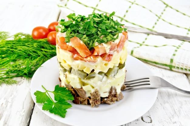 Insalata con manzo, patate bollite, sottaceti, formaggio, pomodoro, prezzemolo nel piatto, tovagliolo, aneto sui bordi di legno leggeri del fondo