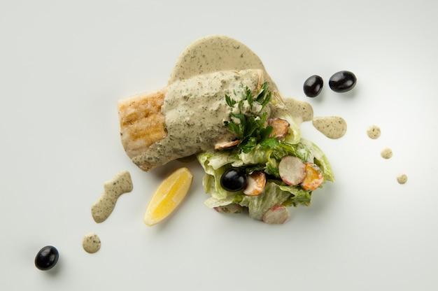 Insalata con olive nere e limone su fondo bianco