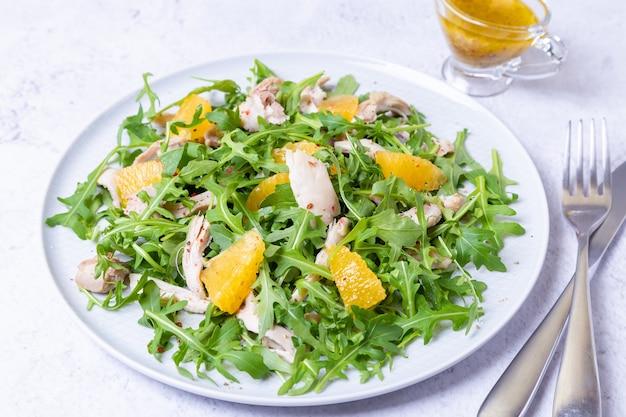 Insalata con pollo, arance e rucola. condimento con olio d'oliva e senape in grani. avvicinamento.