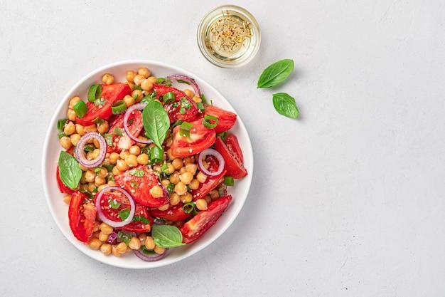 Insalata con ceci, pomodori, basilico e sesamo su fondo grigio chiaro. cibo vegetariano e sano. vista dall'alto, copia dello spazio.