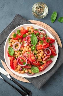 Insalata con ceci, pomodori e basilico in un piatto bianco su sfondo scuro. cibo salutare. vista verticale.