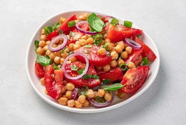 Insalata con ceci, pomodori, erbe fresche, semi di sesamo e olio d'oliva su sfondo grigio. vista laterale, primo piano.