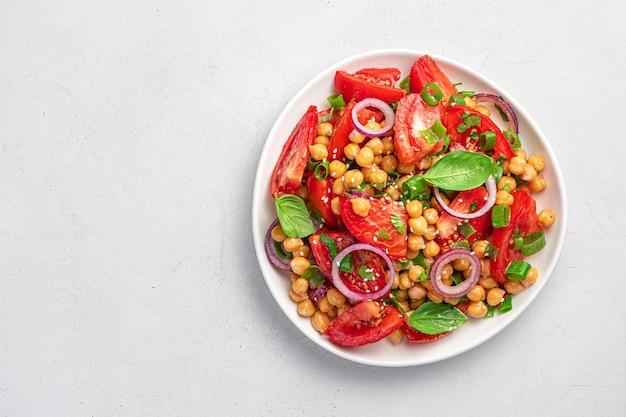Insalata con ceci e pomodori su sfondo grigio. cibo dietetico, sano e vegetariano. vista dall'alto, copia spazio