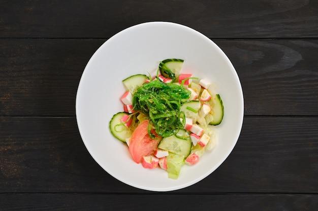 Insalata con polpa di granchio, alghe, pomodori, cetrioli e sesamo sul tavolo di legno scuro