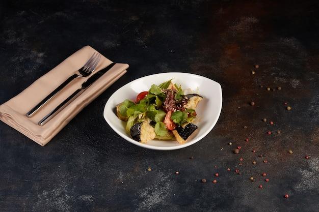Insalata con melanzane, pomodori, paprika, lattuga, sesamo e arachidi su un piatto su sfondo scuro