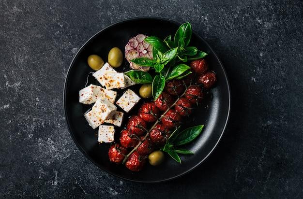 Insalata con formaggio feta e ciliegia al forno, basilico e olive su sfondo nero, messa a fuoco selettiva, vista dall'alto
