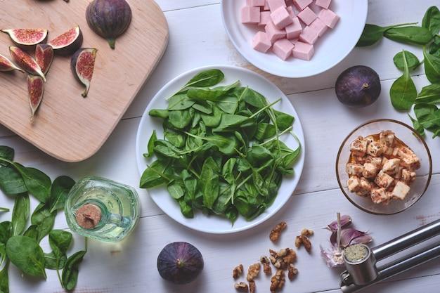 Insalata con fichi ingredienti per il piatto su un tavolo di legno bianco vista dall'alto