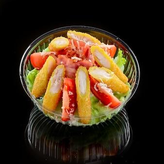 Insalata con pancetta fritta, verdure e pepite su sfondo nero Foto Premium