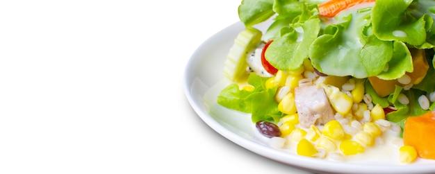 Insalata di frutta e verdura fresca condita con condimento per insalata in un piatto bianco con copia spazio sul lato sinistro