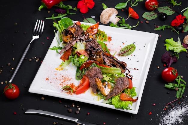 Insalata di manzo alla griglia con verdure grigliate su cuscino con mix di insalata e salsa di senape al miele. su una superficie scura