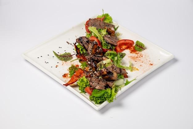 Insalata di manzo alla griglia con verdure grigliate su cuscino con mix di insalata e salsa di senape al miele. su una superficie bianca