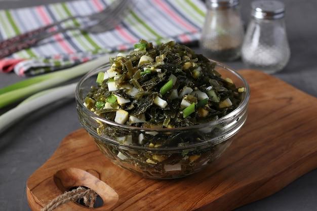 Insalata con alghe, uova e cipolle verdi in una ciotola trasparente su tavola di legno