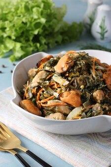 Insalata con alghe, cozze e carote in una ciotola bianca su sfondo azzurro
