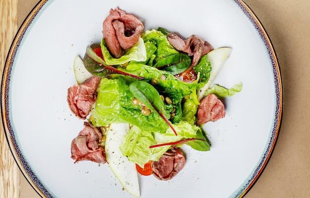 Insalata con lenticchie, carne di manzo, pera sul piatto bianco