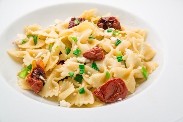 Insalata con maccheroni, pesto, olive, pomodori secchi e rosmarino