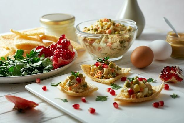 Insalata con maionese, piselli e verdure lesse su fette biscottate, decorata con semi di melograno e prezzemolo