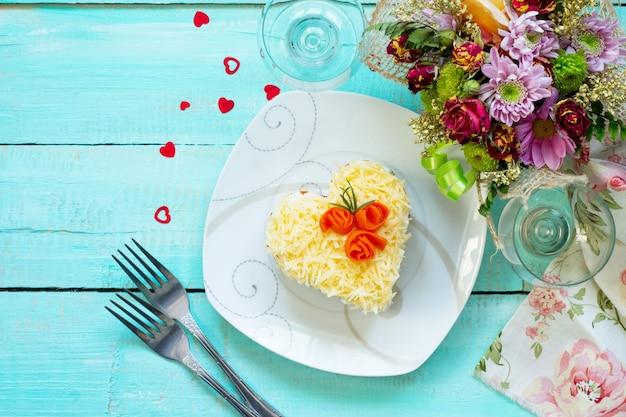 Insalata di carne, funghi, formaggio e verdure sulla tavola festiva il giorno di san valentino.