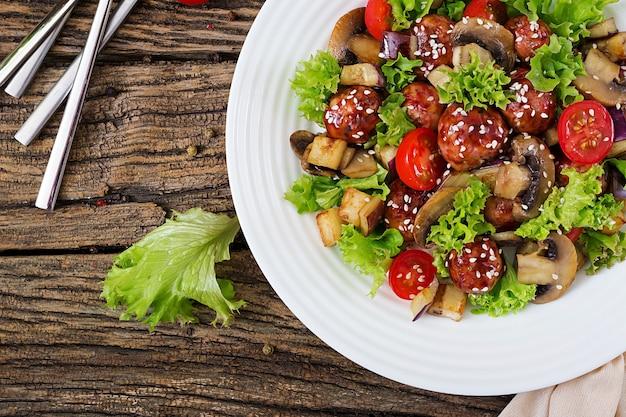 Insalata con polpette, melanzane, funghi e pomodori in stile asiatico. cibo salutare. pasto dietetico. vista dall'alto. disteso.