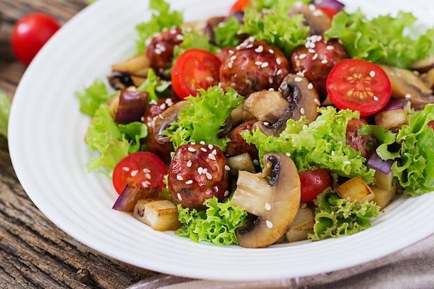 Insalata con polpette, melanzane, funghi e pomodori in stile asiatico.