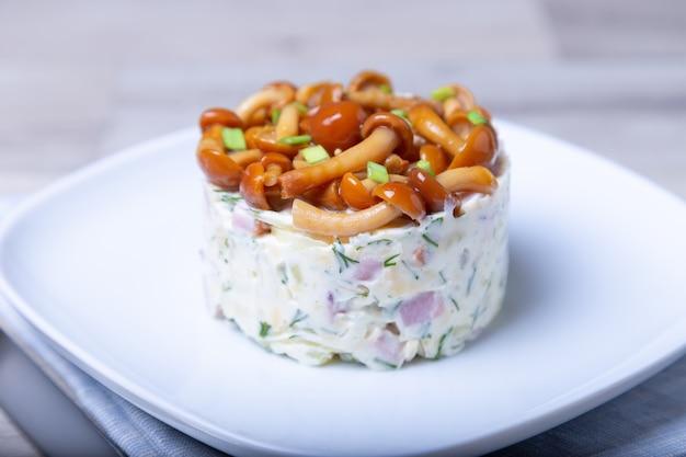 Insalata con funghi (fungo del miele), prosciutto, patate, formaggio e maionese. insalata russa tradizionale «cestino di rafia di funghi». messa a fuoco selettiva, primo piano.
