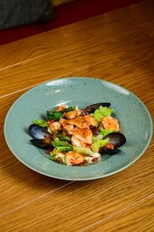 Insalata con ostriche, gamberi e verdure sulla zolla blu su fondo di legno, vista dall'alto