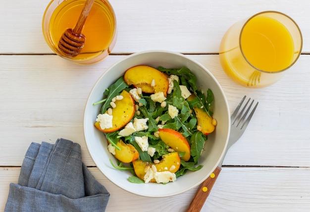 Insalata con pesche, rucola, formaggio, noci e miele. mangiare sano. cibo vegetariano. ricetta.