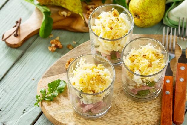 Insalata con pera prosciutto uovo noci frutta e rucola su tavola in legno rustico