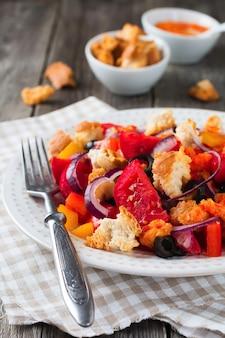 Insalata con peperoni, pomodori, cipolle, olive e crostini di pane con sousomna vecchio fondo di legno. messa a fuoco selettiva.