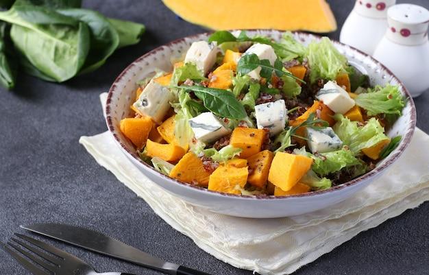 Insalata con quinoa, zucca e formaggio dor blue in un piatto su uno sfondo scuro. avvicinamento