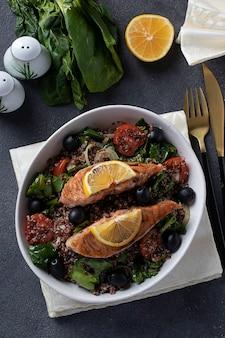 Insalata con quinoa, salmone, spinaci, olive nere, limone e pomodorini in un piatto su superficie grigia