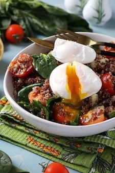 Insalata con quinoa, spinaci, uova in camicia e pomodorini in un piatto su sfondo azzurro. mangiare sano.