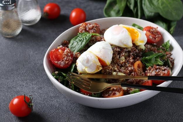 Insalata con quinoa, spinaci, uova in camicia, cetrioli e pomodorini in un piatto su superficie grigia