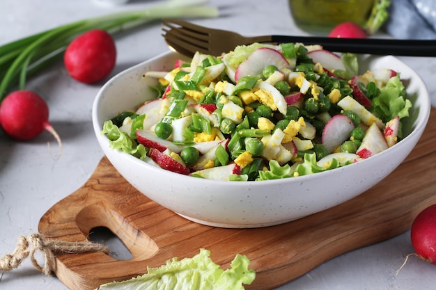 Insalata con ravanelli, cipolle verdi, uova e piselli, condita con olio d'oliva in un piatto su tavola di legno. avvicinamento