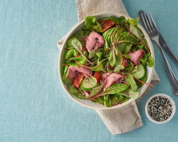 Insalata con carne di roast beef sous vide, pomodori, cetrioli, avocado su tovaglia di lino pastello.