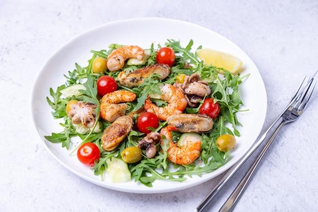 Insalata di frutti di mare, rucola, pomodori, cetrioli e olive su un piatto bianco