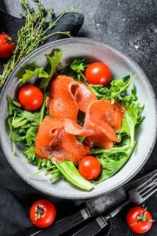 Insalata con salmone affumicato, rucola, avocado e pomodorini. concetto per un pasto gustoso e sano. sfondo nero.