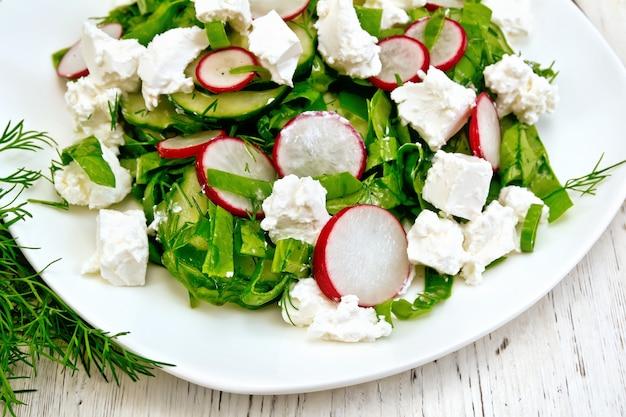 Insalata con spinaci, cetrioli, ravanelli e formaggio salato, aneto e cipolla verde in un piatto sullo sfondo di una tavola di legno
