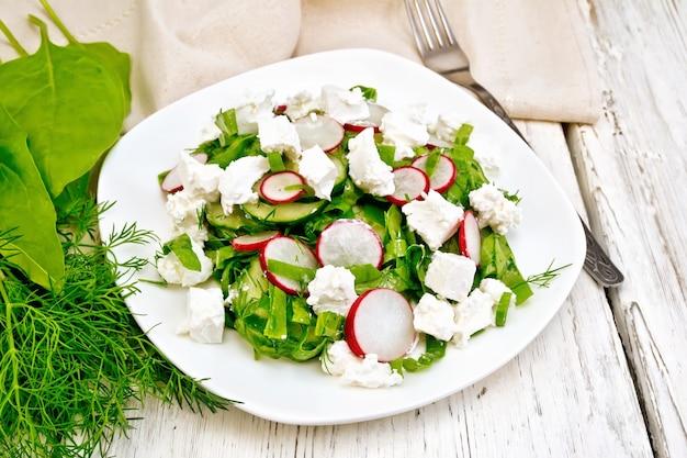 Insalata con spinaci, cetrioli, ravanelli e formaggio salato, aneto e cipolle verdi in un piatto, un asciugamano sullo sfondo di una tavola di legno