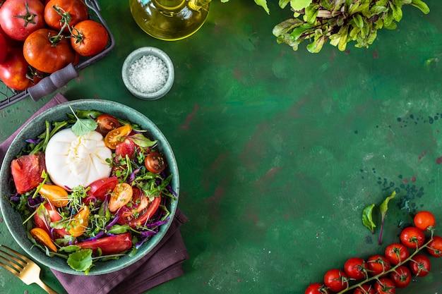 Insalata con pomodori, rucola, burrata e microgreens su uno sfondo di pietra verde, vista dall'alto. copia spazio