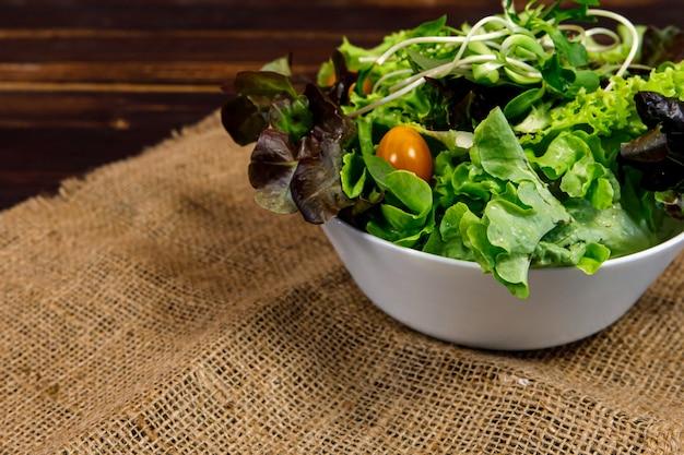 Insalata con una varietà di tipi di verdure naturali in ciotola di legno su fondo di legno. idea menu sano e dietetico.
