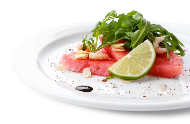 Insalata con anguria, feta, rucola, gamberetti, salsa balsamica su piatto, isolata su bianco