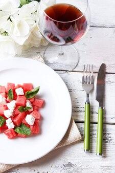 Insalata con anguria, feta e foglie di menta sul piatto, su una superficie di legno