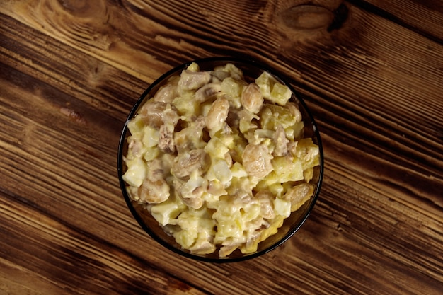 Insalata con fagioli bianchi, patate, carne di pollo, uova e maionese su un tavolo di legno. vista dall'alto