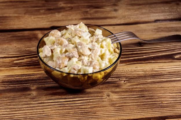 Insalata con fagioli bianchi, patate, carne di pollo, uova e maionese su tavola di legno