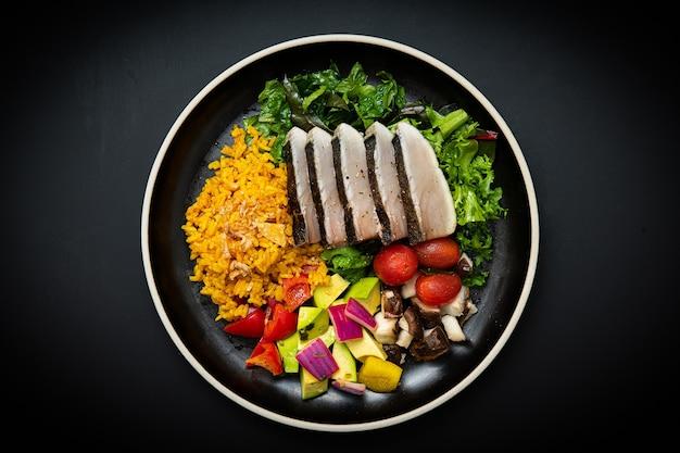 Insalate e verdure varie sono sul piatto bianco lo sfondo è nero