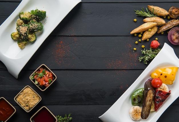 Insalate, cibo vegetale e sugo in piatti su fondo di legno nero