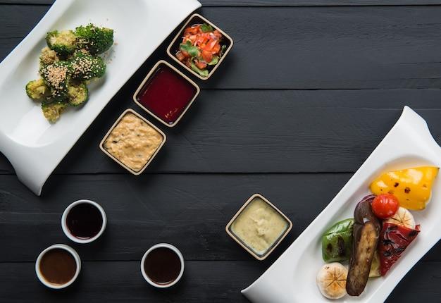 Insalate, alimenti vegetali e salse in piatti su fondo di legno nero