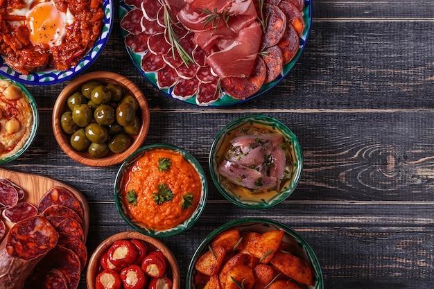 Salame, ciotole con olive, peperoni, acciughe, patate piccanti, purè di ceci su un tavolo di legno.