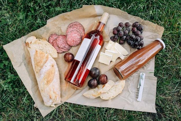 Salame, formaggio, uva, una bottiglia di vino rosato e succo di frutta sull'erba del parco. concetto di cibo e bevande